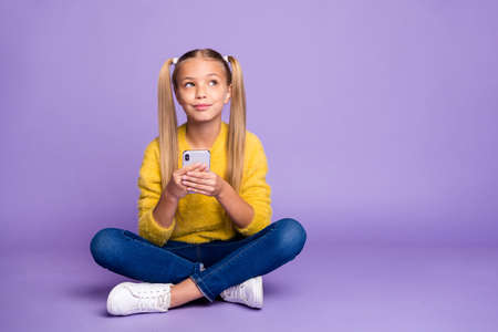 Photo for Full length photo of positive inspired kid sit legs crossed folded use cell phone think post look copyspace wear yellow pullover denim jeans sneakers isolated purple color background - Royalty Free Image