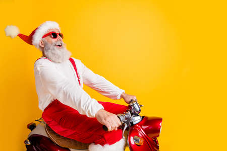 Photo for Profile photo of stylish santa white hair grandpa rushing x-mas theme party by retro bike wear trendy sun specs red trousers cap shirt isolated yellow color background - Royalty Free Image