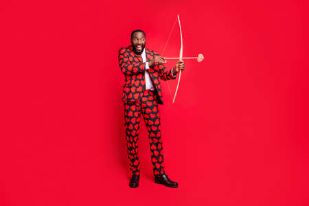 Foto de Full body photo of funny dark skin man with bow and love arrow amour cupid role see good couple wear hearts pattern suit shirt necktie tie boots outfit isolated red color background - Imagen libre de derechos