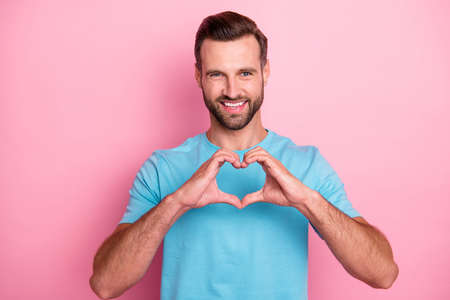 Photo pour Photo of cheerful positive, attractive man showing you heart sign shaped with fingers to show his love to you isolated pastel color background - image libre de droit