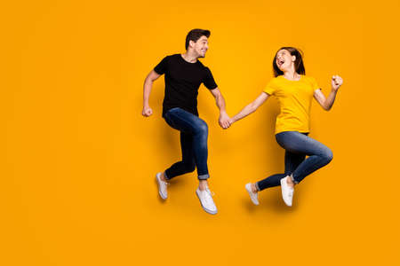 Foto de Full size photo of funny guy and lady couple jumping high rushing mall black friday final discounts season wear casual jeans black t-shirts isolated yellow color background - Imagen libre de derechos