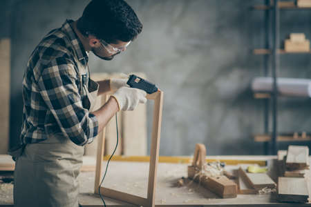 Photo for Profile side photo of serious concentrated worker man use electric hot glue gun to repair wooden construction frame work in home house garage - Royalty Free Image