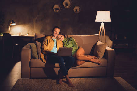 Portrait of his he her she nice attractive cheerful cheery spouses sitting on divan enjoying watching video at night dark home house living-room apartment hotel