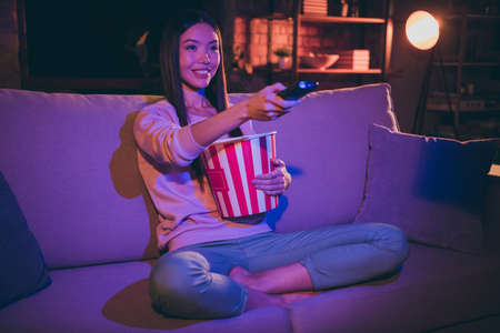 Photo for Photo of pretty lady domestic mood holding tv remote controller changing channels eating popcorn movie night sitting comfy couch casual outfit dark living room indoors - Royalty Free Image