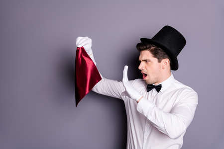Photo pour Profile side photo of funky wizard conjurer hold red napkin say spells want show focus wear white stylish shirt bow tie hat isolated over grey color background - image libre de droit