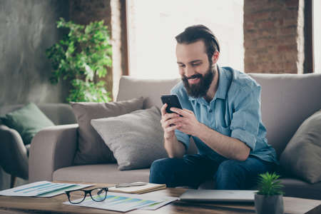 Photo pour Portrait of his he nice attractive cheerful cheery brunet guy sitting on divan typing sms chatting with girlfriend at industrial loft modern style interior room house indoors - image libre de droit