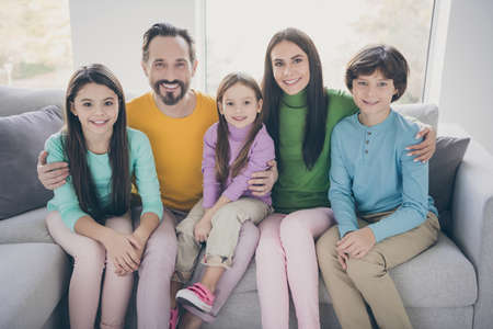 Photo for Positive loving cheerful ideal family concept. Mom daddy sit couch hug embrace her three children schoolboy schoolgirl in house living room - Royalty Free Image