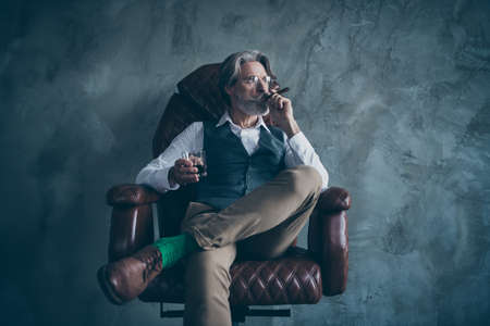 Photo pour Masculine confident old man shareholder sit chair relax hold glass brandy smoke cigarette look wear white shirt brown luxury pants green socks isolated grey concrete wall color background - image libre de droit