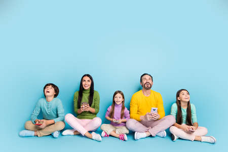 Photo for Nice attractive lovely charming cheerful cheery big full family pre-teen kids sitting in lotus pose using gadget looking up copy space isolated on bright vivid shine vibrant blue color background - Royalty Free Image