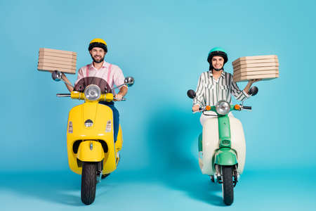 Photo for Full body photo of funny lady guy drive two vintage moped carry pizza boxes courier occupation junk fastfood formalwear outfit protective helmet isolated blue color background - Royalty Free Image