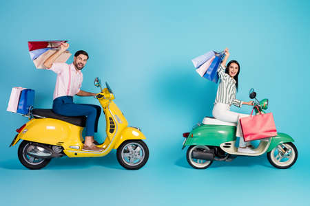 Photo pour Full size profile side photo two people wife husband driver biker drive motor bike transport store mall many bags bought wear formalwear shirt pants trousers isolated blue color background - image libre de droit