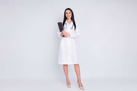 Full body photo of cheerful professional doctor lady rehabilitation clinic holding patient prescription wear long white lab coat stethoscope high-heels isolated grey color background