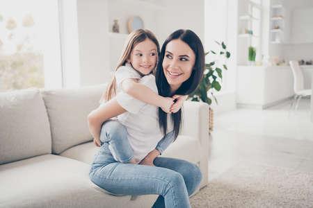 Foto de Photo of candid pretty lovely mother hold her cute little girl kid play game piggyback sit divan in modern light room - Imagen libre de derechos