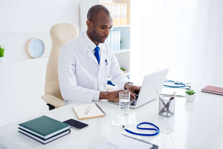 Photo of family doc dark skin guy watch modern technology notebook novelty innovation medical reform cov viral news wear white lab coat sitting chair table office clinic indoors