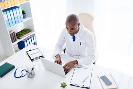 High angle view photo of family doc dark skin guy watch notebook viral news online consultation write prescription patients remote distance assistance wear lab coat office clinic indoors
