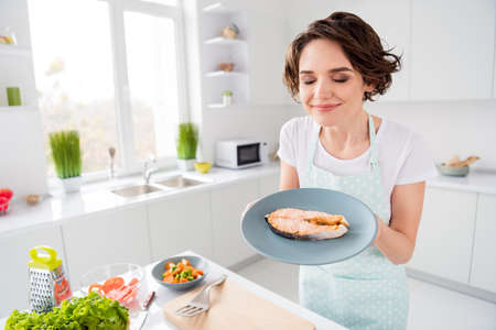 Photo pour Photo of housewife lady chef hold ready grilled salmon trout fillet steak need garnish cook dinner one person portion eyes closed enjoy smell wear apron modern kitchen indoors - image libre de droit