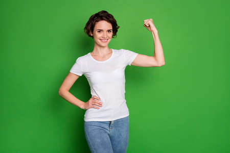 Photo pour Photo of attractive self-confident lady wavy bobbed hairdo demonstrating perfect shape biceps arm win competition wear casual white t-shirt jeans isolated bright green color background - image libre de droit