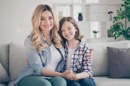 Foto de Photo of domestic charming blond lady mommy daughter sitting comfy couch hold arms stay home quarantine spend weekend together hugging best friends living room indoors - Imagen libre de derechos