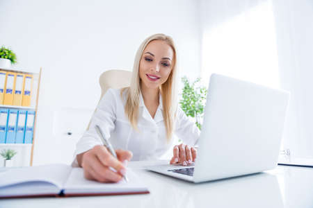 Photo for Portrait of her she nice-looking attractive cheerful focused experienced girl doc writing notes plan to-do list visit using laptop in modern light white workplace workstation - Royalty Free Image