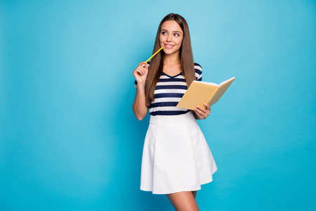 Photo for Photo of beautiful cheerful lady hold diary copybook pen noting creative thoughts look empty space curious pencil on chin wear striped t-shirt white skirt isolated blue color background - Royalty Free Image
