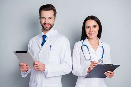 Photo pour Photo of handsome busy family doc guy lady virology clinic listen client experienced doctors write paper online prescription tablet clipboard wear lab coats isolated grey color background - image libre de droit