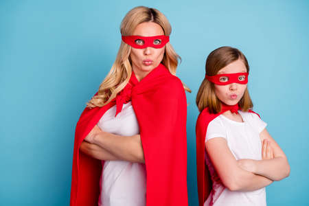 Foto de Photo of confident mommy lady little daughter sending air kisses carnival super woman girl costumes arms crossed incredible heroes wear s-shirts red coat masks isolated blue color background - Imagen libre de derechos