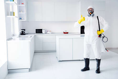 Photo pour Full size photo of confident successful guy cleaner show in gloves coverall thumb up symbol approve stop spread ncov epidemic treatment wear boots yellow latex gloves goggles in house kitchen indoors - image libre de droit