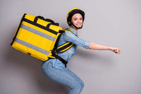 Photo for Profile side photo of positive girl courier drive scooter concept deliver client food meal pizza hold thermo backpack wear denim jeans shirt helmet isolated over gray color background - Royalty Free Image
