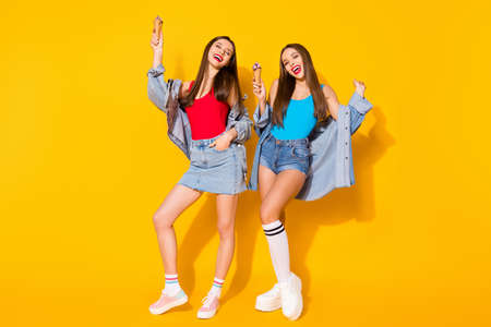 Foto de Full length photo positive cheerful funky girls sisters have fun spring time weekend holiday hold ice cream cones wear blue red tank-top denim isolated bright shine color background - Imagen libre de derechos