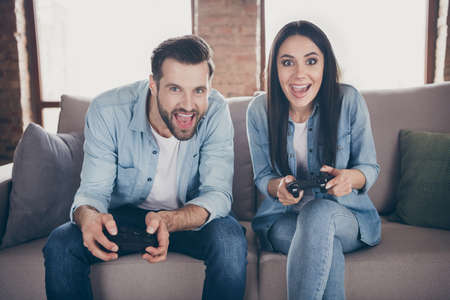 Photo for Portrait of his he her she nice attractive lovely excited glad cheerful friends friendship sitting on divan playing videogame having fun at modern brick loft industrial interior house flat - Royalty Free Image