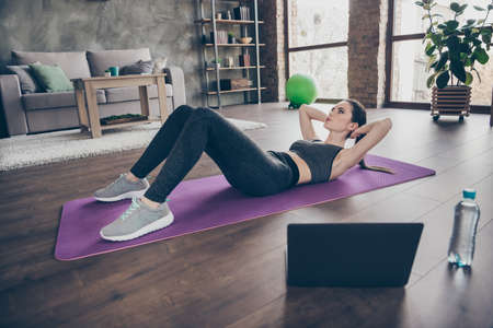 Full size photo of focused active sporty athletic beautiful girl doing video online workout laptop aerobics exercise crunches pilates on floor mat in house indoors