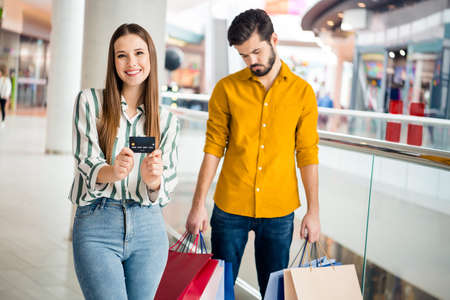 Photo pour Portrait of his he her she nice attractive lovely positive cheerful cheery couple bored sad guy carrying things girl holding in hands bank card walking having fun - image libre de droit