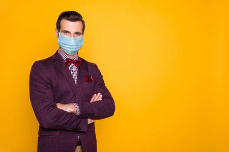Portrait of his he nice attractive healthy guy wearing gauze safety mask mers cov disease prevention social distance folded arms copy space isolated bright vivid shine vibrant yellow color background