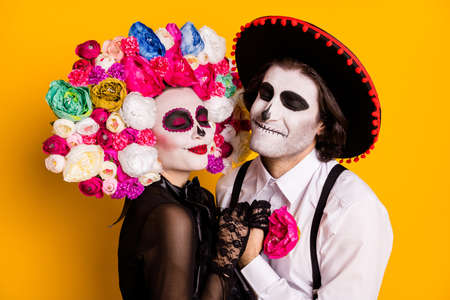 Foto de Everlasting love. Closeup photo of cute lovely dead couple man lady hold hands wear black lace dress gloves death costume roses headband suspenders sombrero isolated yellow color background - Imagen libre de derechos