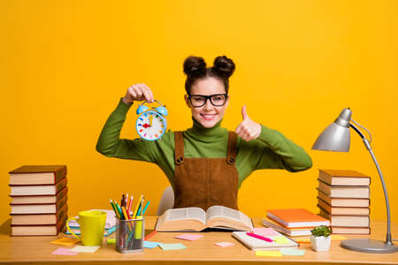 Photo for Photo of positive girl high school student sit table prepare exam hold clock show thumb up sign wear green sweater isolated over bright shine color background - Royalty Free Image