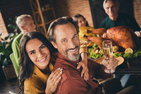 Photo pour Congratulations. Photo of full family gathering bristled father wife embrace shiny smiling hold wineglass drink champagne served dinner big table generation in evening living room indoors - image libre de droit