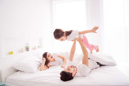 Photo pour Photo of amazing young family lady guy hold arms little girl mommy daddy daughter lying sheets having fun good mood spend together quarantine weekend bedroom indoors - image libre de droit
