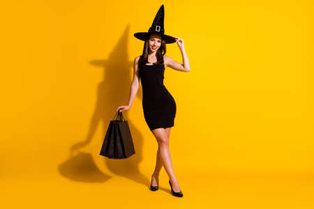 Foto de Full length body size view of her she nice attractive pretty thin cheerful chic lady wizard carrying new things clothes touching cone hat isolated bright vivid shine vibrant yellow color background - Imagen libre de derechos