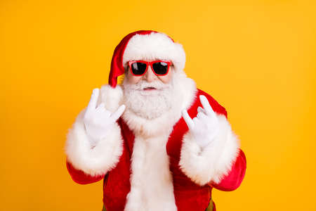 Foto de Close-up portrait of his he nice funny cool naughty white-haired Santa St Nicholas showing double horn sign heavy metal isolated over bright vivid shine vibrant yellow color background - Imagen libre de derechos