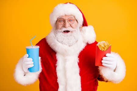 Photo for Close-up portrait of his he nice cheerful cheery glad funny white-haired Santa enjoying eating fastfood menu meal drinking cola isolated over bright vivid shine vibrant yellow color background - Royalty Free Image