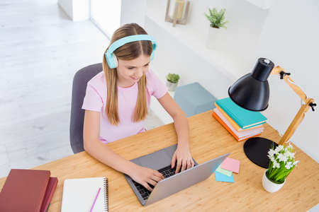 Foto de Top above high angle view photo little kid girl study remote use laptop text type have online communication conversation tutor have headset sit comfort cozy table desk in house indoors - Imagen libre de derechos