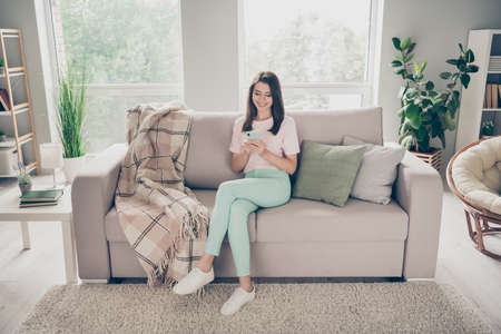 Photo pour Photo portrait of modest woman sitting on couch with crossed legs holding phone in two hands indoors - image libre de droit