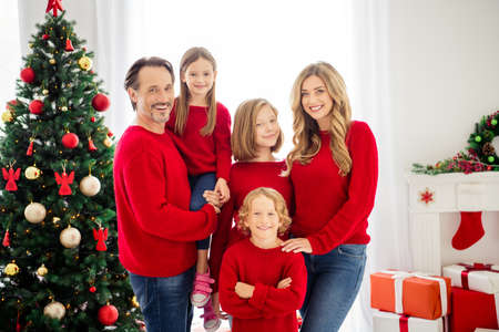 Photo of full family five people gathering three small kids father hold embrace daughter boy crossed arms wear red sweater in evening living room x-mas tree lights present boxes indoors
