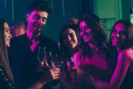 Photo pour Photo portrait of students drinking champagne together clinking glasses in neon light - image libre de droit