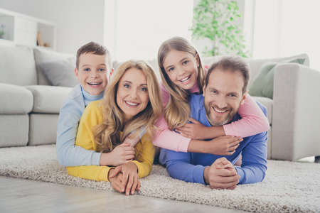 Photo pour Photo of positive cheerful mommy daddy lying carpet hug two kids boy girl piggyback in house indoors - image libre de droit