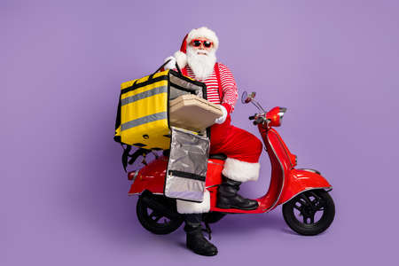 Photo pour Photo of santa claus drive moped hold pizza box backpack wear x-mas costume striped shirt cap specs isolated purple color background - image libre de droit