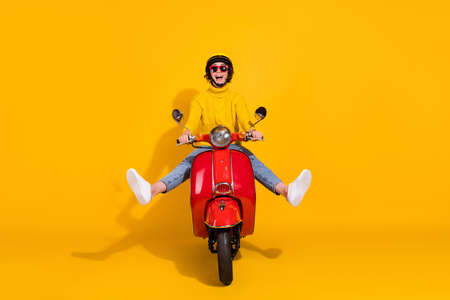 Photo pour Photo portrait of funny girl driving red retro motorbike spreading legs isolated on vivid yellow colored background - image libre de droit