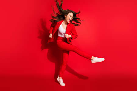 Photo for Full length profile photo of lovely young lady wind blow hair raise knee wear jacket trousers sneakers isolated red color background - Royalty Free Image