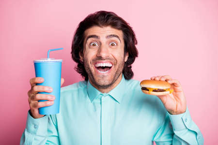 Photo pour Photo portrait of smiling man holding soda and cheeseburger isolated on pastel pink colored background - image libre de droit