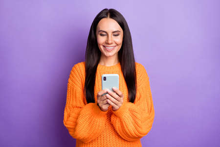 Photo pour Portrait of charming positive girl hold phone typing comment wear pullover isolated on purple color background - image libre de droit